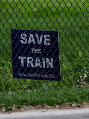 "A sign that reads, ""Save the Train"" is placed inside"
