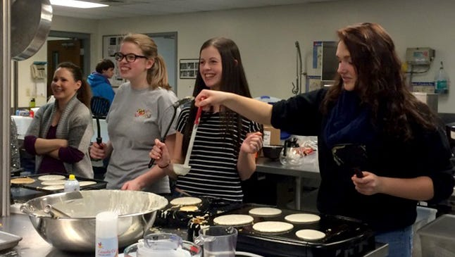 From left, Billie Jo Roberts, Hannah Stum, Kelly Porter and Sydney Delpi prepare food for the 2015 Shrove Tuesday pancake dinner at Grace UMC, as Derek Charleton, background, ponders his next assignment.