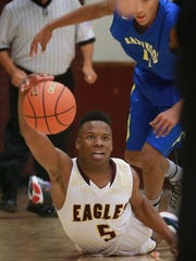 Andress' Malcolm Lewis, bottom, reached for a loose ball in front of Eastwood's Chris Nobles Tuesday.