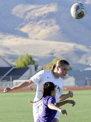 Defender Katelyn Howerton heads the ball over Yerington's Maria Castro.