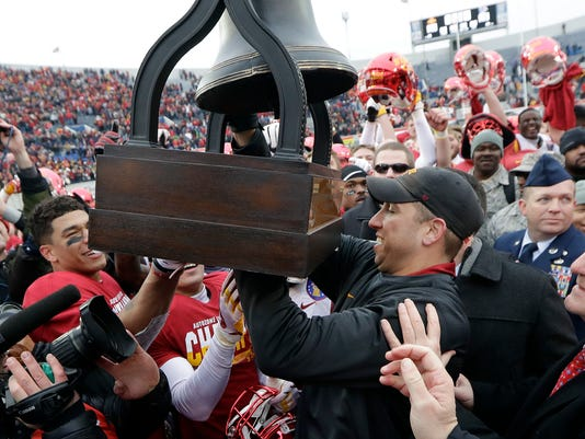 Iowa State head coach Matt Campbell, right, passes the winners' trophy over to his players after beating Memphis in the Liberty Bowl NCAA college football game, Saturday, Dec. 30, 2017, in Memphis, Tenn. Iowa State won 21-20. (AP Photo/Mark Humphrey)