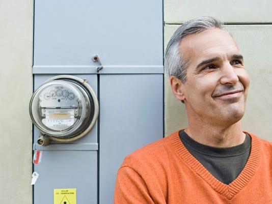 Smiling man beside electric meter