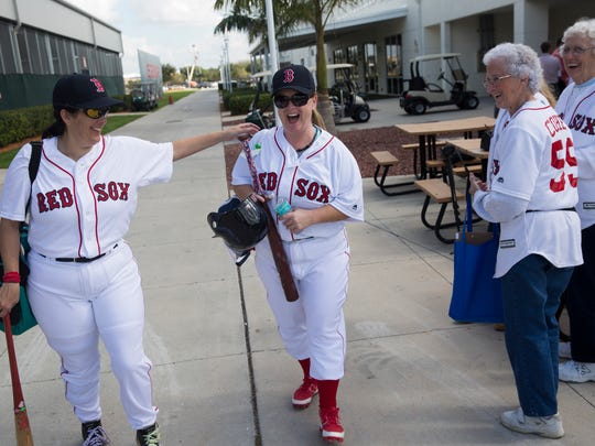 """Teammates and members of """"The Peaches"""" Tina Trahan, left, from Rhode Island, and Amy Modglin, center, a native of Boston, share a laugh as they make their way to the field for their first round matchup during the Women's Fantasy Baseball Camp at JetBlue Park Thursday, Jan. 12, 2017 in Fort Myers, Fla."""