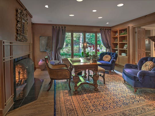 The wood-paneled library has a fireplace, built-in shelves and cabinets, a hardwood floor and recessed lights.