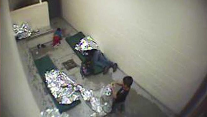 This September 2015 file image made from U.S. Border Patrol surveillance video shows a child crawling on the concrete floor near the bathroom area of a holding cell, and a woman and children wrapped in Mylar sheets at a U.S. Customs and Border Protection station in Douglas, Ariz. The Department of Homeland Security is reviewing whether it should keep immigration detention facilities under private operators amid pressure from immigration activists to end the practice.