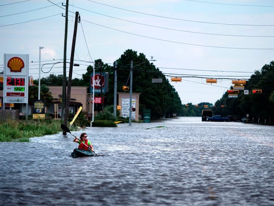 A woman paddles down a flooded road while shuttling