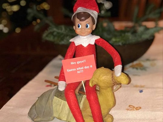 "Elf on the Shelf having fun on a Wednesday. The sign says, ""Hey guys! Guess what day it is?"""