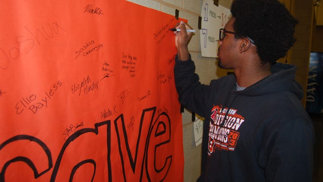 Indian Hill High School senior Zarian Hunter Cure signs his name and adds a message of encouragement to a banner students at the school prepared to show their support for Withrow University High School.