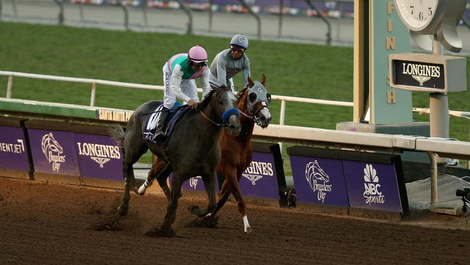 Arrogate ridden by jockey Mike Smith races to the finish line past California Chrome ridden by jockey Victor Espinoza during the Breeders' Cup Classic race on Day 2 of the 2016 Breeders' Cup World Championships at Santa Anita Park on Nov. 5, 2016.