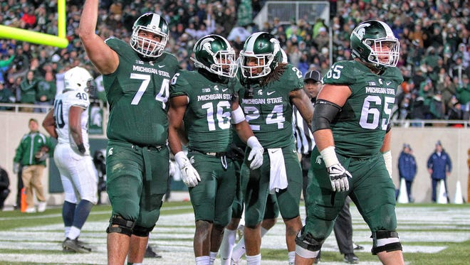 Offensive tackle Jack Conklin and Michigan State wide receiver Aaron Burbridge and running back Gerald Holmes and offensive lineman Brian Allen celebrate a touchdown during the 2nd half of a game against the Penn State Nittany Lions at Spartan Stadium.