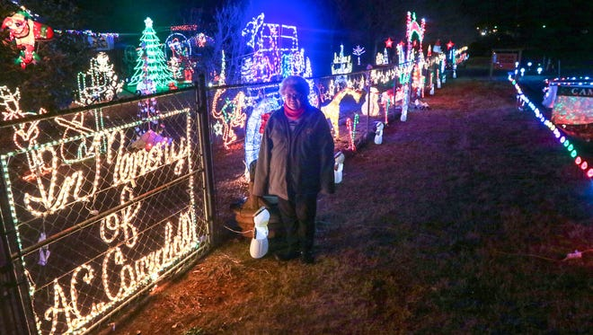 Virginia Campbell stands near a display of Christmas lights along S.C. Highway 24 in Westminster. Campbell said that after her husband A.C. Campbell passed away nearly 30 years ago, she would set up more lights in his memory.