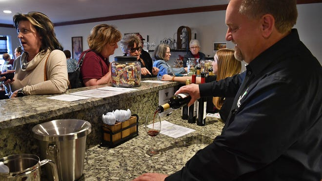 Scott Poenitzszh, owner and general manager of Horseshoe Bend Cellars Vineyard and Winery, pours a glass of wine during the grand opening Friday. The business is located on Peterson Road and was formerly Wichita Falls Vineyard and Winery.