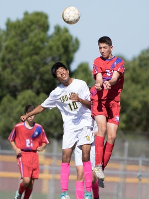 Las Cruces High's Gael Fernandez pops a header as Mayfield's Angel Soto eyes the ball during boys prep soccer Saturday at the Field of Dreams Soccer Complex.