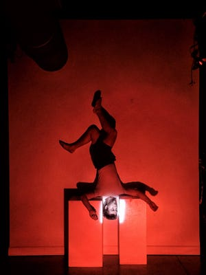 """Dalton Hedrick of Boots on the Ground Theater goes upside down as part of a day's work in Ken Jones' """"Darkside."""" The production about a troubled mission to the moon opens at the Derek Gores Gallery on July 19."""