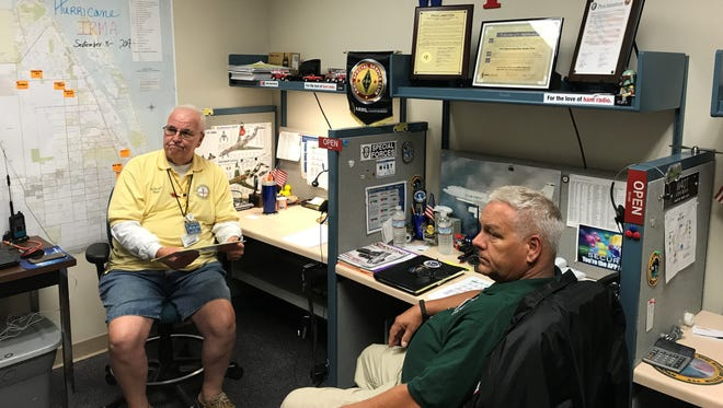 Amateur radio operators Paul Bartoszewicz (yellow shirt) and willie Thompson (green) at the Indian River County EOC on Sunday.