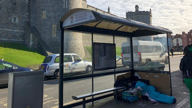 A homeless man sleeps in a bus shelter in the shadow of Windsor Castle on Feb. 7.