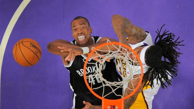 Brooklyn Nets center Jason Collins, left, battles for a rebound with the Lakers' Jordan Hill during the first half on Sunday.