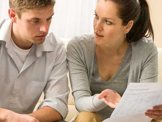 Young couple sits on couch reviewing paperwork.