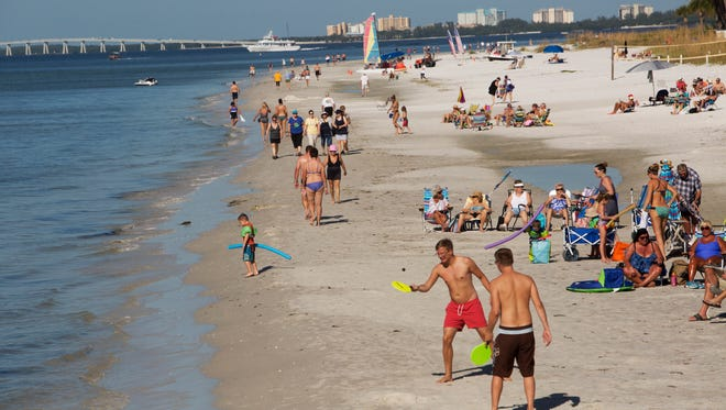 Visitors to Fort Myers Beach enjoy cooler temperatures and dry weather on Thursday.