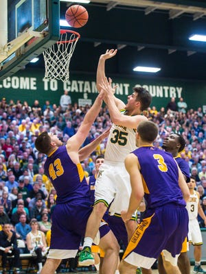 The University of Vermont's Payton Henson, center, shoots over the University of Albany's Greig Stire in Burlington on Wednesday, February 22, 2017.