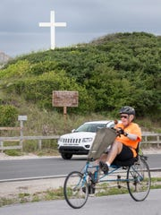 People ride past the Island Cross on Fort Pickens Road