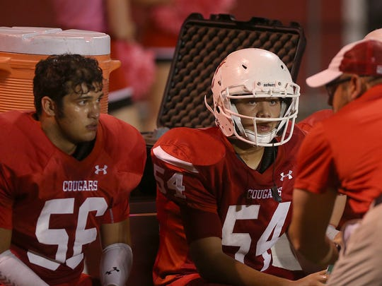 Christoval Cougars Diego Salinas (#56) and Colton Clevenger listen to their coach on the sideline during Friday night's game against the Eldorado Eagles in Christoval, Oct. 13, 2017. Christoval won 31-0.