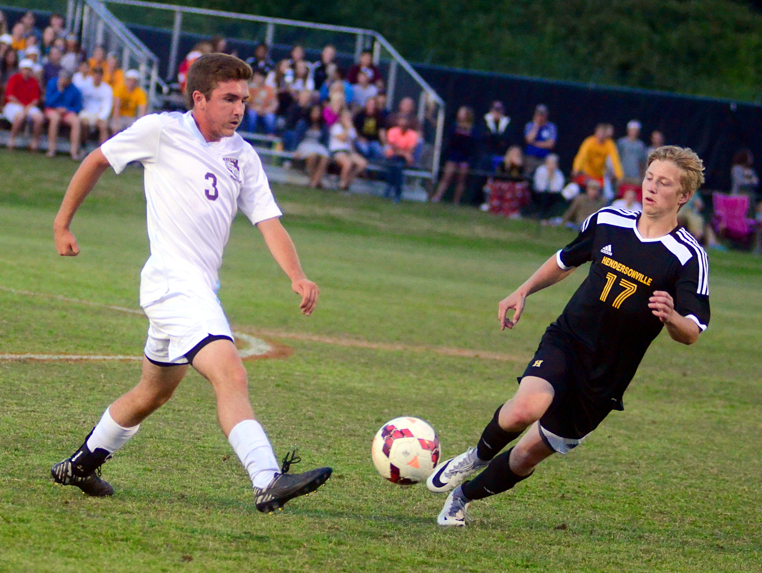 Station Camp High senior Mark Ludwig plays the ball away from Hendersonville senior Darius Campbell during first-half action.