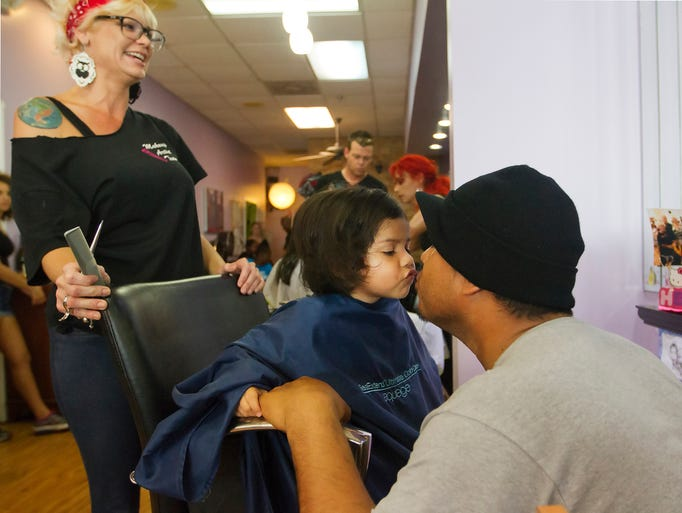Jennifer Meyers, left, styled Aliana Zavala's hair so well that the 2-year-old gave her father, Ivan, a thank you kiss Sunday during the Back to School Cut-A-Thon at Indulgence Salon in Fort Myers. More than 20 area students received free hair cuts from Meyers and other stylists at the salon.