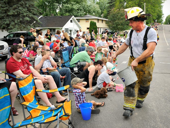 Sauk Rapids firefighter Jason Adamski gives out a handful of andy to he children along the parade route of the Rapids River Days parade through Sauk Rapids  Friday.