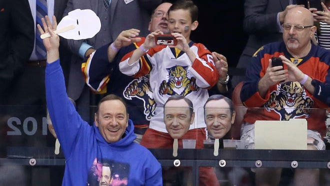 Actor Kevin Spacey waves to the fans during an NHL hockey game between the Florida Panthers and the Detroit Red Wings in Sunrise, Fla., Saturday, March 19, 2016.