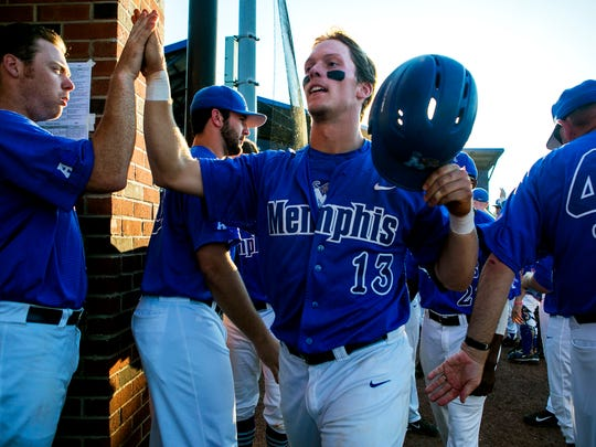 Chris Carrier, a senior right fielder for the University of Memphis, is congratulated by his team after hitting a home run during a game against Murray State at FedExPark on Tuesday. The baseball player has overcome injuries to lead his team this year.