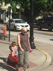 A woman pulls a child in a wagon through Collingswood's business district.