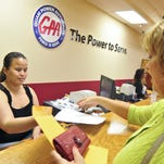 In this file photo, Guam Power Authority cashier Nadine Cruz, left, accepts a utility payment from customer Marla Baldwin. The power agency is preparing to launch a new program that rewards customers  who install eligible energy efficient appliances.