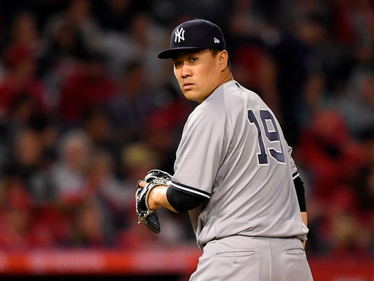 Yankees starting pitcher Masahiro Tanaka checks first after walking the Angels' Mike Trout during the sixth inning on Saturday, April 28, 2018, in Anaheim, Calif.