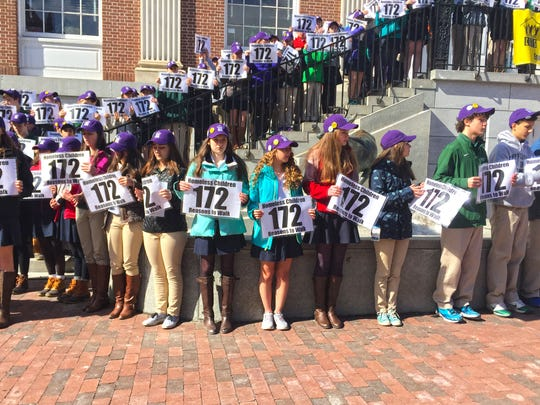 Rice Memorial High School students stand in front of Burlington City Hall on Thursday holding numbers to represent the number of homeless children in Chittenden County.