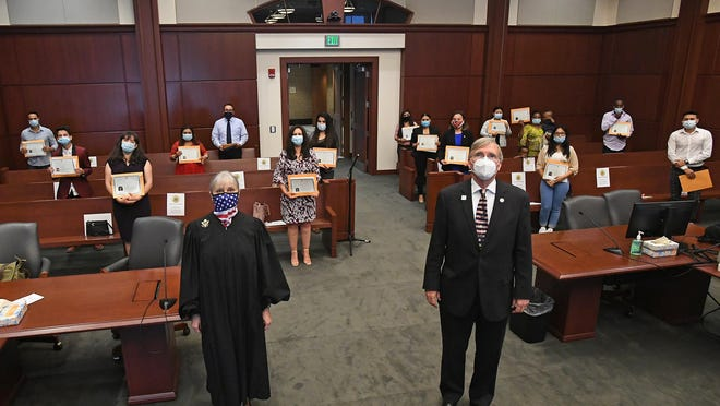 Hailing from 10 countries, 16 new U.S. citizens are shown Friday following a citizenship and naturalization ceremony at U.S. District Court in Erie. Presiding over the ceremony was U.S. District Judge Susan Paradise Baxter, at left. Speaking at the event was Erie Mayor Joe Schember, at right.