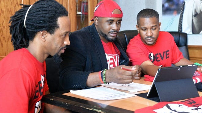 Birdgang Brand partners, from left, Ronald C. Wilson, Brian K. Scott, and Danny L. Mosby, look over their website design during a meeting in Louisville, Ky., Tuesday, June 23, 2015.