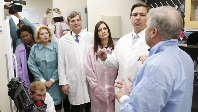 State officials learn about testing procedures on potential coronavirus cases at the Florida Department of Health Laboratory in Tampa. Deputy Secretary for Health, Dr. Shamarial Roberson (from left); state Sen. Janet Cruz; state Surgeon General, Dr. Scott Rivkees; Lt. Gov. Jeanette Nunez; and Gov. Ron DeSantis look on while Andrew Cannons, laboratory director at the Bureau of Public Health Laboratories, speaks.
