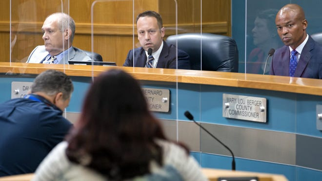 Palm Beach County Vice Mayor Robert S. Weinroth (left), Mayor Dave Kerner and Commissioner Mack Bernard listen to Angelique Contreras, a mask opponent, speak at the commission meeting on Tuesday where commissioners unanimously voted to require people to wear masks in public.
