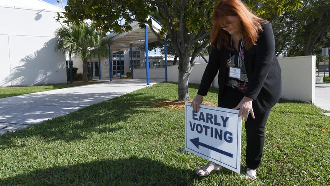 Linda Moreno sets up voting signs outside the Ezell Hester Community Center in Boynton Beach so that early voting can take place in the 2020 Presidential Preference Primary. Saturday, March 7, 2020.
