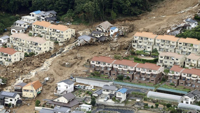 In this aerial photo, a rescue helicopter hovers  over an area devastated by a massive landslide in Hiroshima, western Japan, Wednesday, .