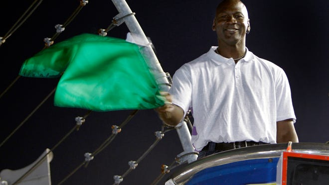 Michael Jordan practices waving the green flag before a NASCAR All-Star auto race at Charlotte Motor Speedway in 2010. Denny Hamlin is starting his own race car team in partnership Jordan and Bubba Wallace as the driver.
