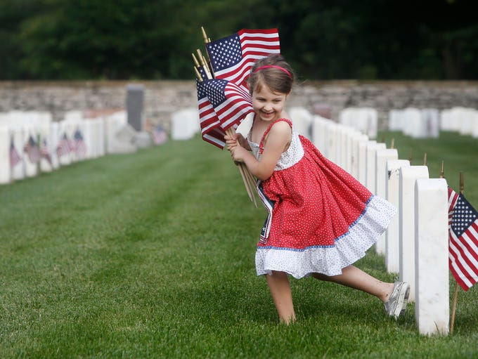 Delaney Gardner, 6, runs with a hand full of flags