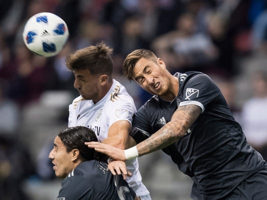 Los Angeles FC's Dejan Jakovic, back left, vies for the ball against Vancouver Whitecaps' Jose Aja, right, and Efrain Juarez during the first half of an MLS soccer match Friday, April 13, 2018, in Vancouver, British Columbia. (Darryl Dyck/The Canadian Press via AP)