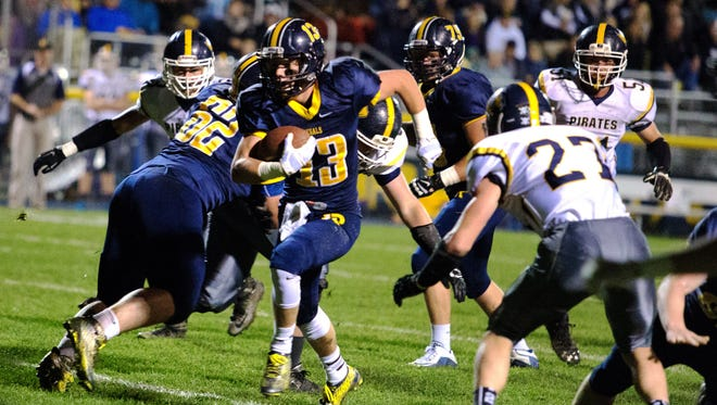 Iowa City Regina's Ethan Suchomel (13) breaks a run deep into Hudson territory during the first half of play in Iowa City during the first half of play on Monday, November 2, 2015.