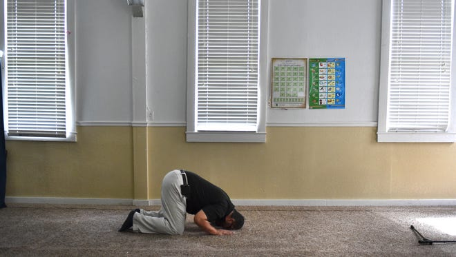 "Mohammad Malik, of Port St. Lucie, prays in solitude inside the mosque at the Islamic Center of Fort Pierce on Midway Road on June 1, 2017. ""It's just a one-on-one connection with God,"" he said. ""Putting my head down on the ground is a sign of humility, and acknowledging the superiority of God."" He was in the building behind the fire-damaged mosque that was destroyed by arson Sept. 12, 2016."
