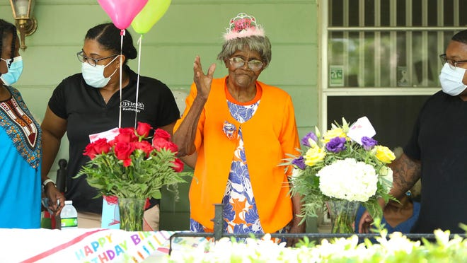 Doretha Bryant waves to family and friends as they drive by her house for a 100th birthday celebration held for Bryant at her home in Hawthorne on Friday. The family held a drive-by birthday celebration to lower the risk of spreading COVID-19.