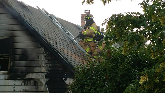 Firefighters work to extinguish a house fire in Dallas Sunday evening.