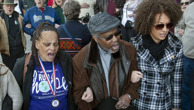 "From left to right: Della Montgomery-Riggins, Charles Thornton and Rachel Dolezal link arms and sing ""We Shall Overcome"" at a rally in downtown Spokane, Wash., March 2015."