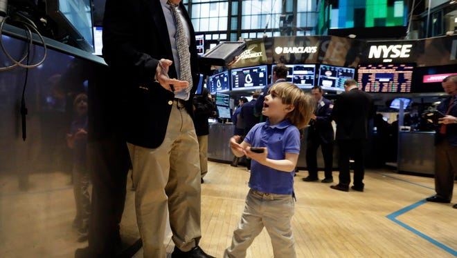 Tripp Mancuso, 4, works with his trader father Peter Mancuso on the floor of the New York Stock Exchange, during the NYSE Working Parents/Caregivers Employee Resource Group's annual Take Your Child to Work Day program, Thursday, April 24, 2014. Mixed earnings from a large number of U.S. companies left the stock market without direction early Thursday, despite positive results from a handful of names including Apple and Caterpillar. (AP Photo/Richard Drew) ORG XMIT: NYRD101